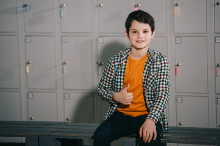 Smiling brunette kid showing thumb up while posing in locker room