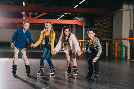 Adorable smiling children preparing to start moving on roller skates Zdjęcie Seryjne