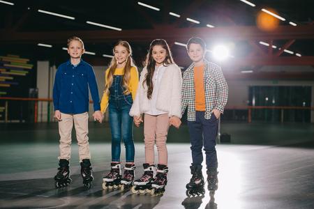 Cute smiling children in roller skates standing on spacious roller rink Zdjęcie Seryjne