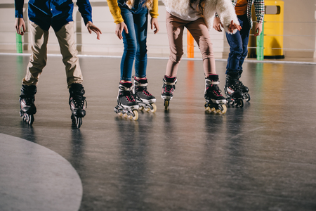 Cropped view of children preparing to start moving in roller skates