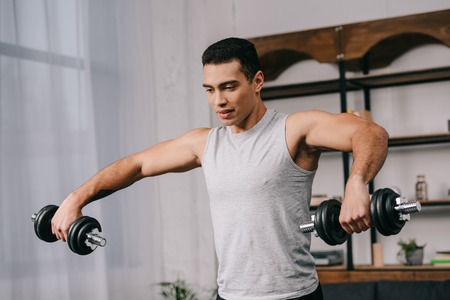handsome bi-racial man doing exercise with dumbbells in living room