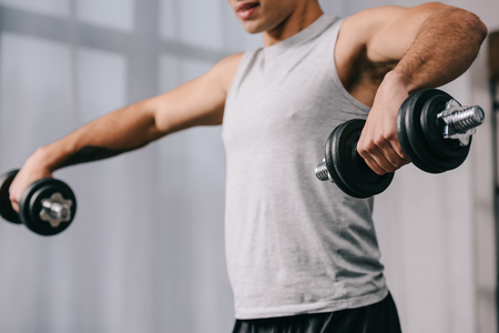 cropped view bi-racial man workout with dumbbells