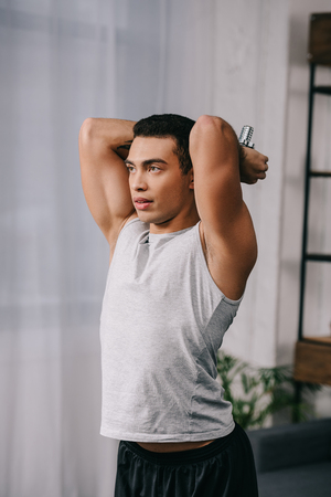handsome bi-racial man in sportswear workout with dumbbell