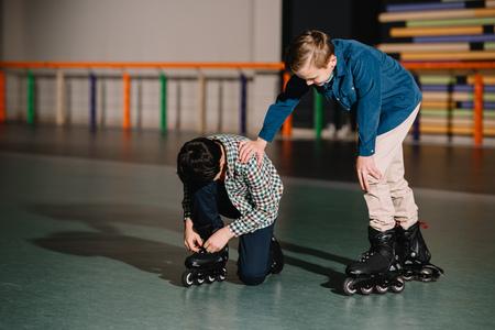 Pretty careful boy helping friend in fixing roller skate boot