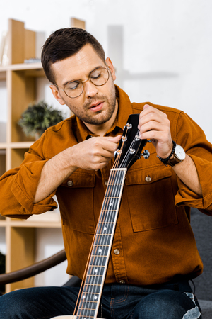 handsome man in glasses tuning acoustic guitar at home Фото со стока