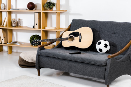 modern living room with acoustic guitar, ball and remote control on sofa