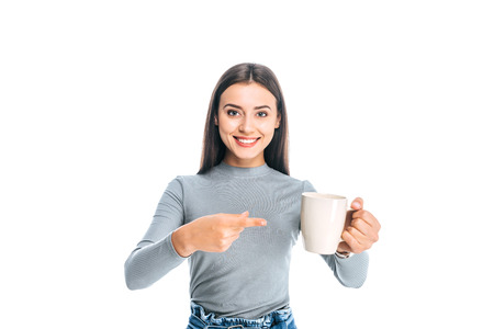 portrait of young woman pointing at cup of coffee isolated on white Imagens