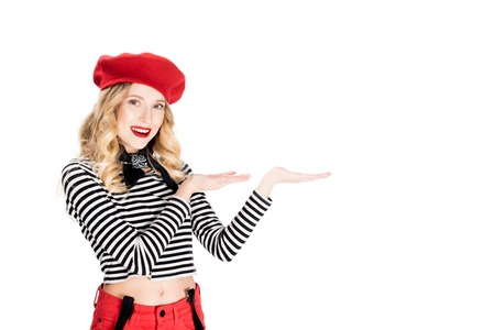 attractive woman in red beret showing something isolated on white