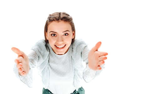 high angle view of attractive smiling woman with outstretched arms looking at camera isolated on white