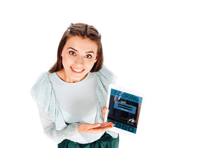 high angle view of smiling young woman with tablet with booking lettering isolated on white