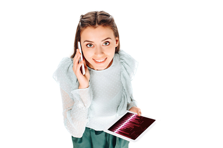 high angle view of smiling woman with tablet talking on smartphone isolated on white