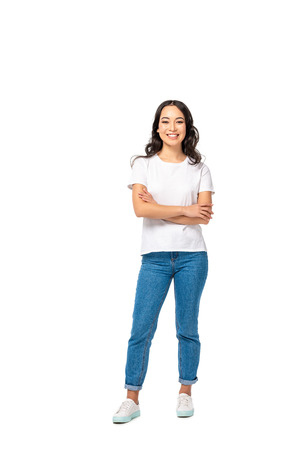 Smiling asian young woman in white t-shirt and blue jeans standing with crossed arms isolated on white Stock Photo