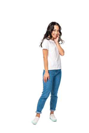 Shy asian woman in white t-shirt and blue jeans holding hand near face isolated on white