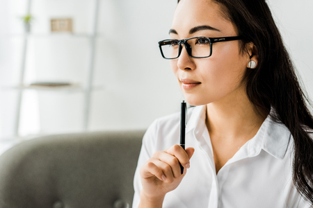 beautiful asian businesswoman in formal wear and glasses holding pen and looking away in office