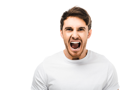 emotional young man screaming and looking at camera isolated on white