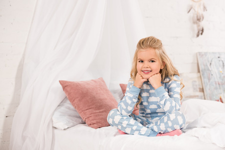 smiling cute kid sitting on bed with crossed legs and hands near face Stock Photo