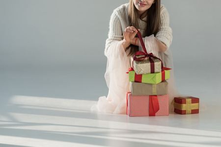 cropped image of woman in fashionable winter outfit squatting near gift boxes and opening present on white