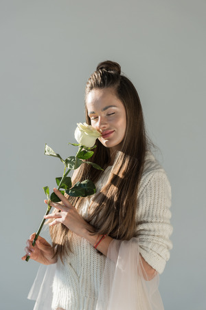 attractive woman in fashionable winter outfit sniffing white rose with closed eyes isolated on white Imagens