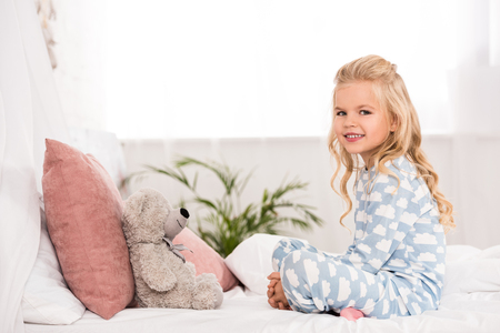 cute child sitting on bed with crossed legs and teddy bear
