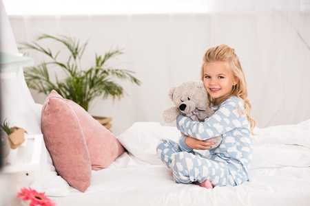 cute child sitting on bed with crossed legs and hugging teddy bear Stock Photo