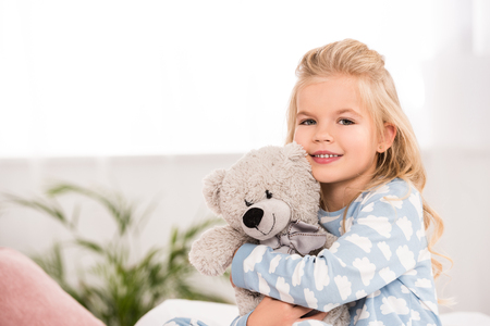 adorable child hugging teddy bear in bedroom