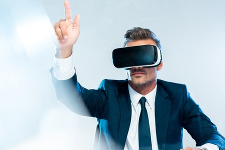 businessman in virtual reality headset touching something isolated on white, artificial intelligence concept Stock Photo