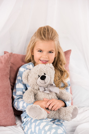 cheerful cute kid embracing teddy bear in bed Stock Photo