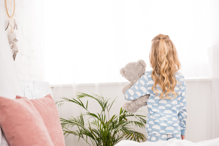 back view of child in pajamas standing with teddy bear in bedroom Stock Photo