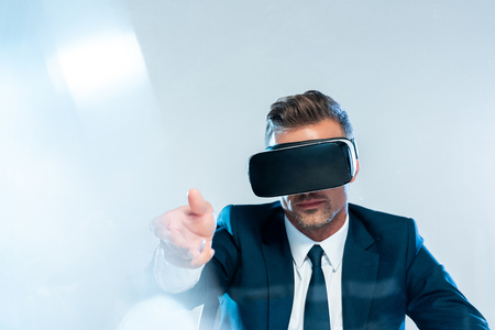 businessman in virtual reality headset taking something isolated on white, artificial intelligence concept Stock Photo