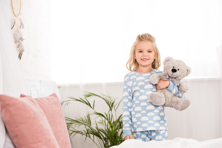 smiling child in pajamas standing with teddy bear in bedroom
