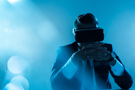 businessman in virtual reality headset sitting isolated on blue, artificial intelligence concept Stock Photo