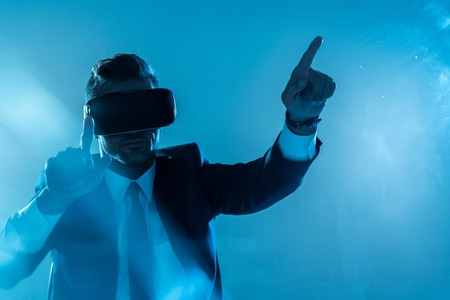 businessman in suit and virtual reality headset touching something isolated on blue, artificial intelligence concept