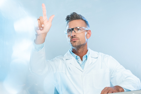 handsome scientist in protective glasses touching something isolated on white, artificial intelligence concept Stock Photo