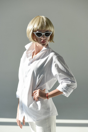 attractive blonde woman in sunglasses and fashionable white outfit standing with hand akimbo on white Stock Photo