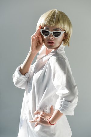 attractive blonde woman in sunglasses and fashionable white outfit looking at camera isolated on white