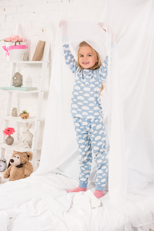 smiling kid in pajamas standing on bed and touching canopy
