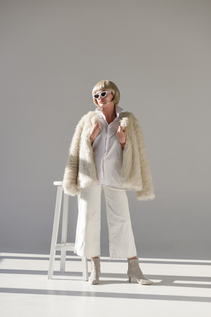 attractive blonde woman in sunglasses and fashionable winter outfit with faux fur coat standing near chair on white
