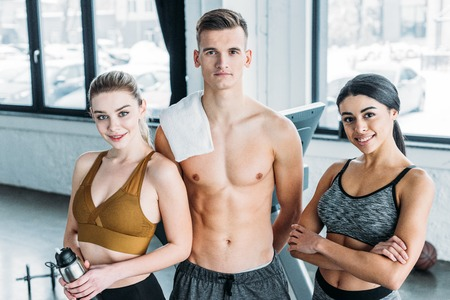 shirtless male trainer and beautiful multiethnic sportswomen smiling at camera in gym
