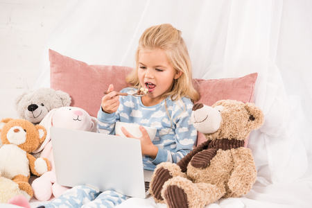 cute child eating cornflakes and watching cartoons in bed