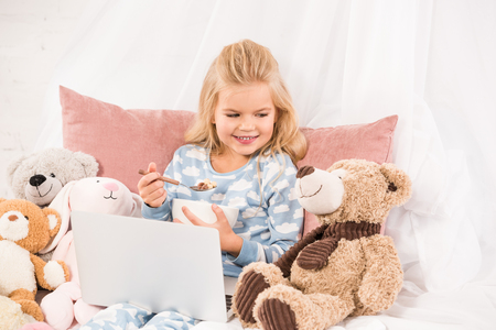 cute child with laptop eating cornflakes and looking at teddy bear in bed Stock Photo