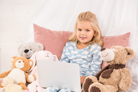 adorable child sitting in bed with soft toys and watching cartoons Фото со стока