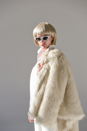portrait of attractive blonde woman in sunglasses and fashionable winter outfit with faux fur coat looking at camera on white