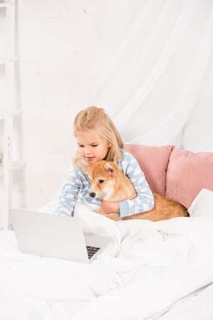 adorable child lying in bed, hugging corgi dog and using laptop at home