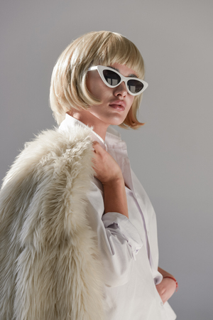 portrait of attractive blonde woman in sunglasses and fashionable winter outfit with faux fur coat looking away isolated on white