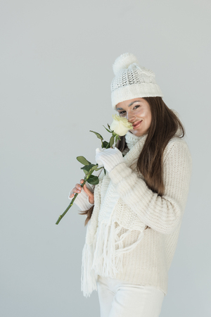 attractive woman in fashionable winter sweater and scarf sniffing white rose and looking at camera isolated on white Imagens