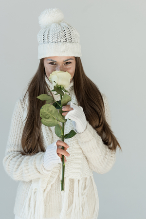 beautiful girl in fashionable winter sweater and scarf sniffing white rose and looking at camera isolated on white
