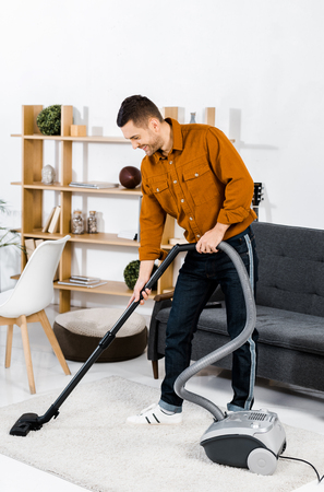 handsome man in modern living room smiling and cleaning house with hoover Stok Fotoğraf