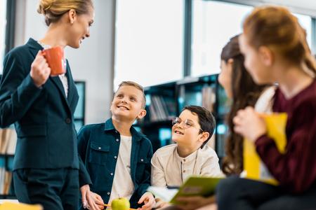 smiling librarian looking at cute schoolchildren in library 版權商用圖片