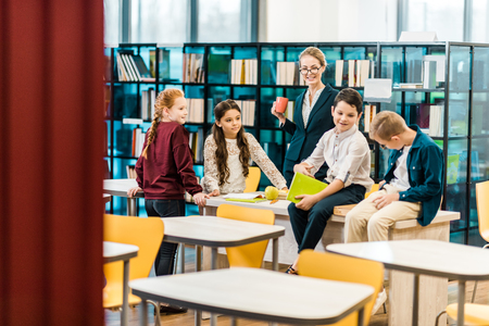 adorable schoolchildren and young female librarian standing and sitting in library 写真素材 - 117855403