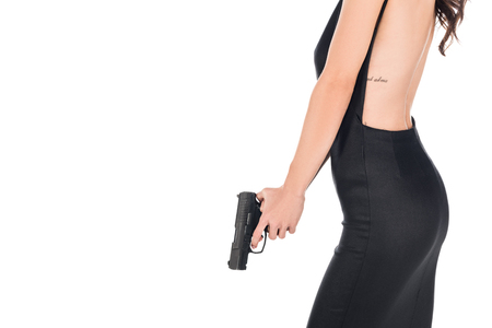 cropped view of female killer in black dress holding gun, isolated on white